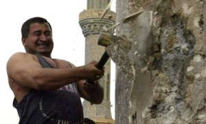 Kadom al-Jabouri swings a hammer at the base of the statue of Saddam Hussein in Baghdad in April 2003. Photograph: Jerome Delay/AP